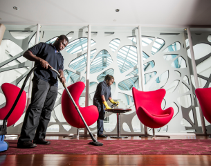 2 Mitie staff members cleaning reception area of corporate offices