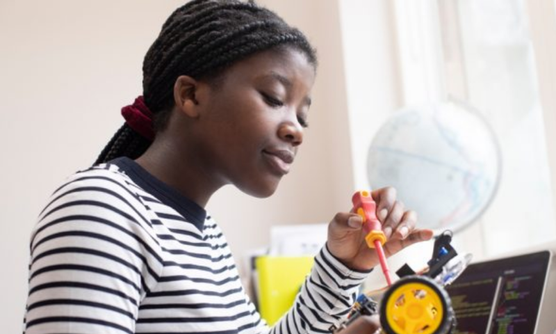 Black female young person fixing a model wheel