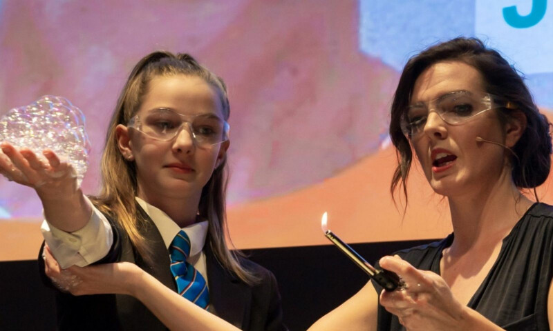 A schoolgirl at a science show doing an experiment
