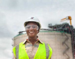Black female Bechtel employee standing in front of propane tank construction