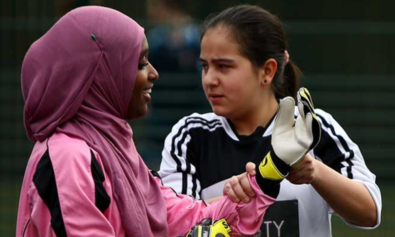 2 female young people, one with head scarf playing football