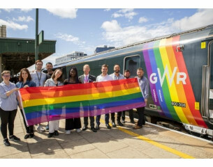 Group of people stood holding a pride flag by a train painted in the Pride colours