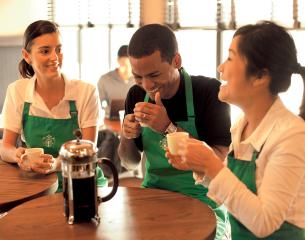3 Starbucks baristas around a table enjoying coffee