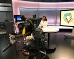 Behind the scene shot of a studio with a female presenter