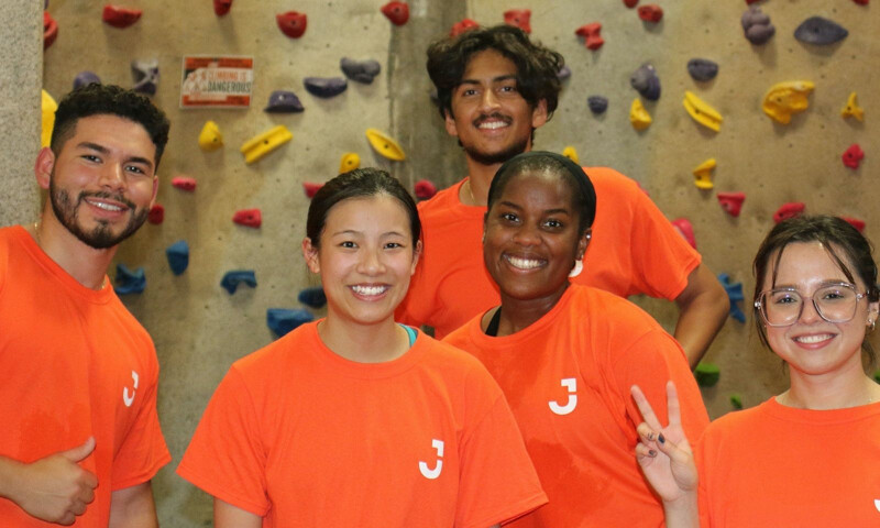 5 interns wearing orange t-shirts smiling at the camera stood in front of a climbing wall