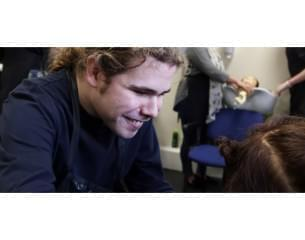 Image of North East Autism Society helping an autistic man learn to be a hairdresser
