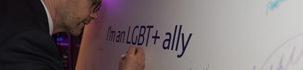 Image of a man signing the LGBT+ ally board