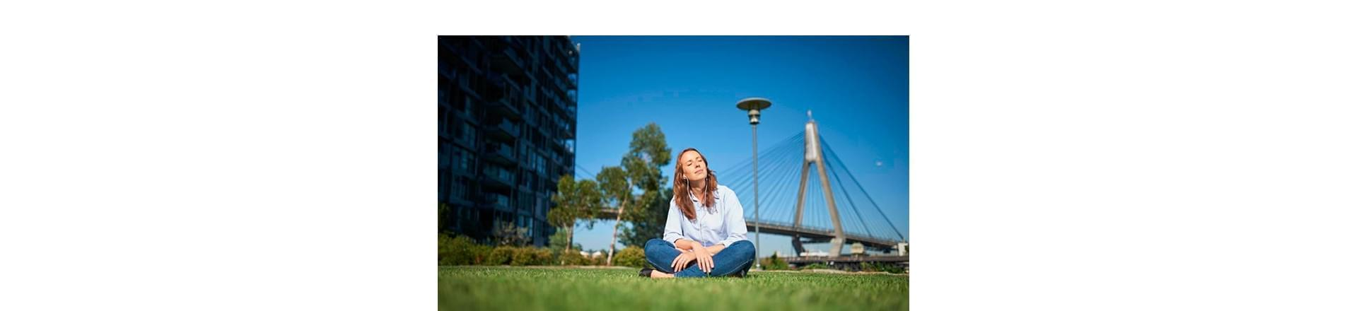 Woman sat in a field with green grass and blue sky with a building in the background