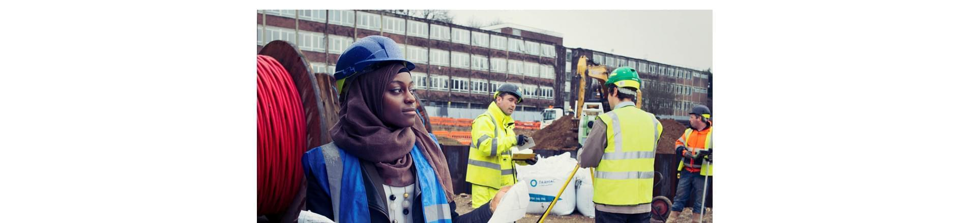 Fauzia on the building site in head scarf and protective headwear holding a plastic bag