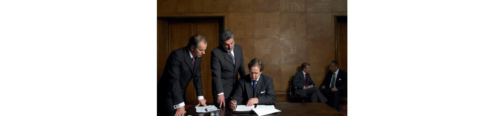 Group of men in suits stood and sat around a table with papers in front of them