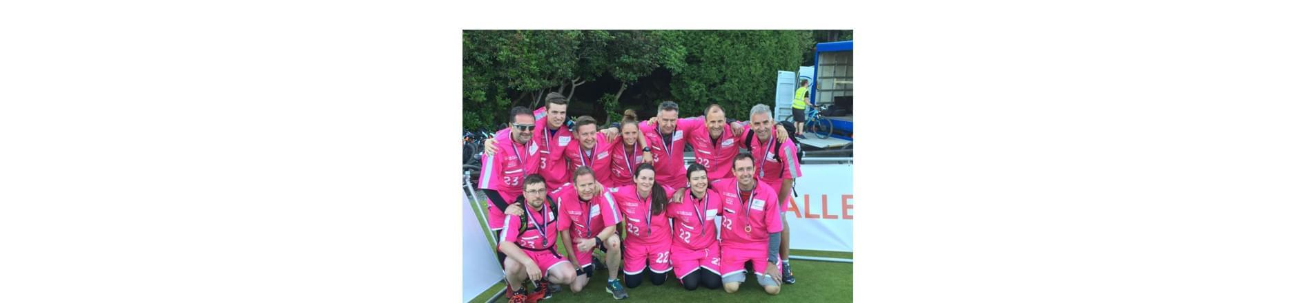 T-Systems employees who took part in the UK Challenge 2017. They are wearing magenta outfits and medals.