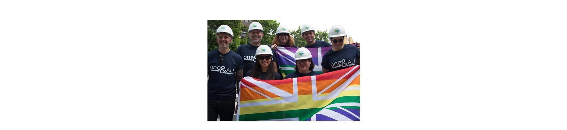 a group of seven Lendlease employees wearing Lendlease branded hard hats. They are holding British rainbow flags and wearing tops that read 'One and All'.