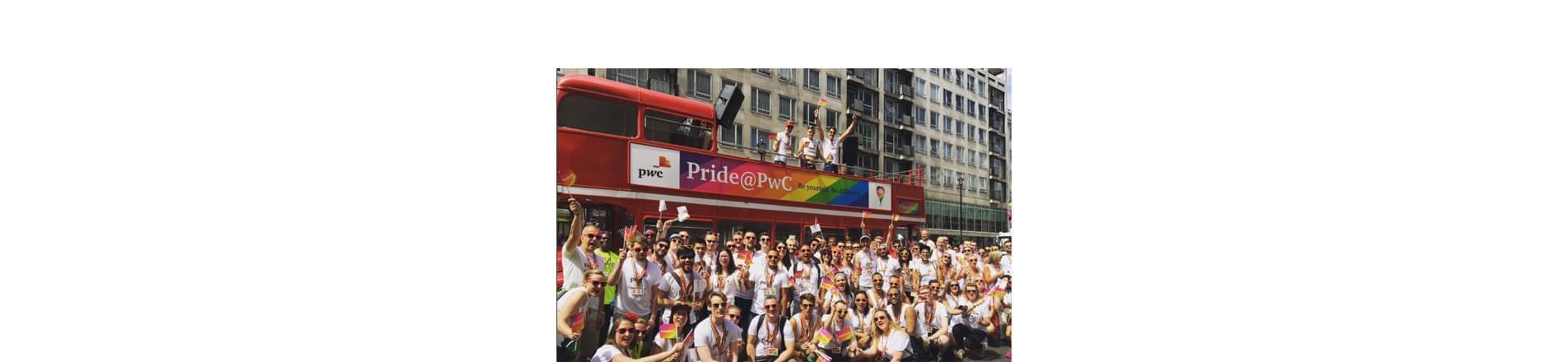 a group of PwC employees standing in front of a red open-top London bus with the Pride @ PwC rainbow branding.