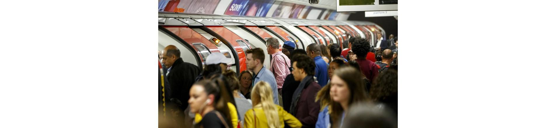 a busy London tube platform full of a diverse mix of commuters.